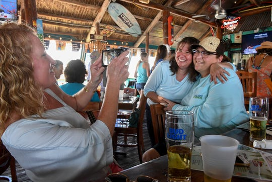 "Nicole Cheyne (left) snaps a picture of Wendy Browning (center) and Michelle Sigmon as the group of friends from Fort Pierce enjoy their last time at The Original Tiki Bar & Restaurant  seated in the middle among a full house of patrons during the Tiki Bar's final day of business on Sunday, April 28, 2019, in Fort Pierce. ""Tiki Bar is going to be missed,"" Sigmon said. ""We've had a lot of memories here over the years, lots of birthday, we've had anniversaries, we've come to celebrate Friday Fest and listen to our friends jam in bands over the years. It's just a great town and we're going to miss this spot.""  Nicole Cheyne, Wendy Browning, Michelle SIgmon"