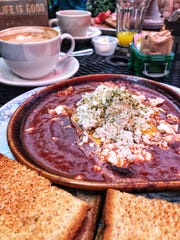 Shakshooka (eggs baked in spicy tomato sauce with Bulgarian feta and Mediterranean herbs) and coffee served on the patio at Art Cafe of Nyack.