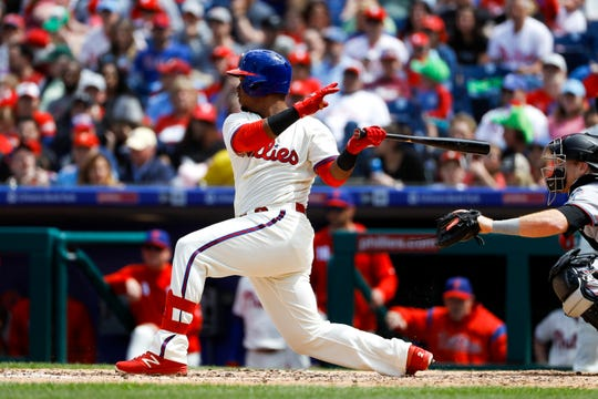 Philadelphia Phillies' Jean Segura follows through after hitting a RBI-triple off Miami Marlins starting pitcher Pablo Lopez during the third inning of a baseball game, Sunday, April 28, 2019, in Philadelphia.