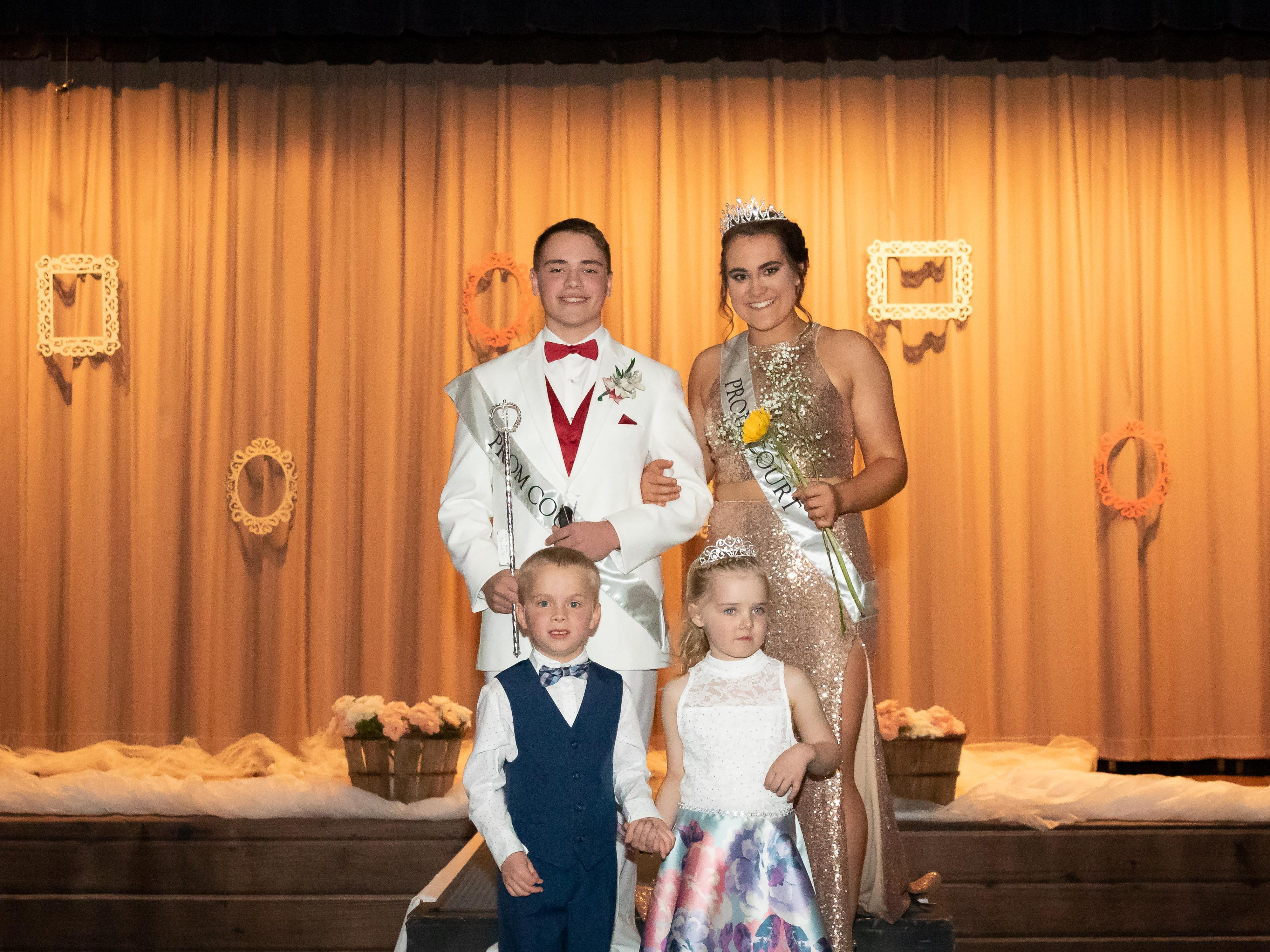 Prom King Jaret Hartley and Queen Calli Statz pose for a photo with miniature prom court members Logan Breu and Lux Lobner during the Assumption High School prom on Saturday, April 27, 2019, at the high school in Wisconsin Rapids.