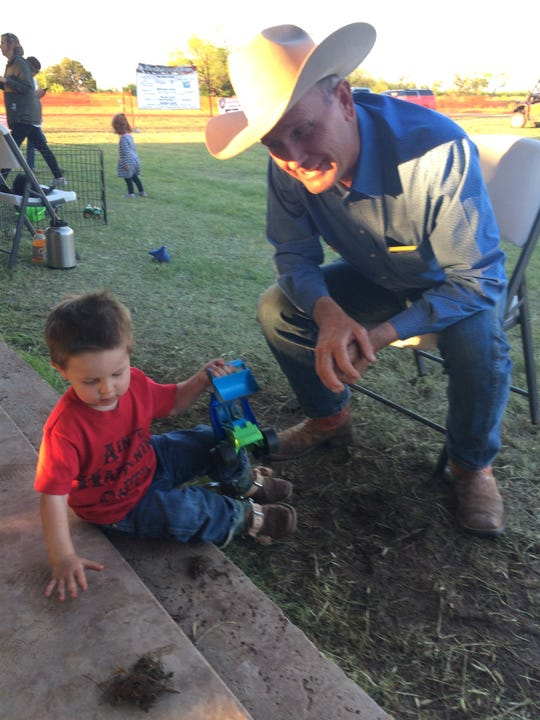 Jerry Bob Daniel plays with his grandson Auggie after dinner Friday evening. Daniel hosts the annual veteran helicopter hog hunt on his Truscott, Texas, ranch.