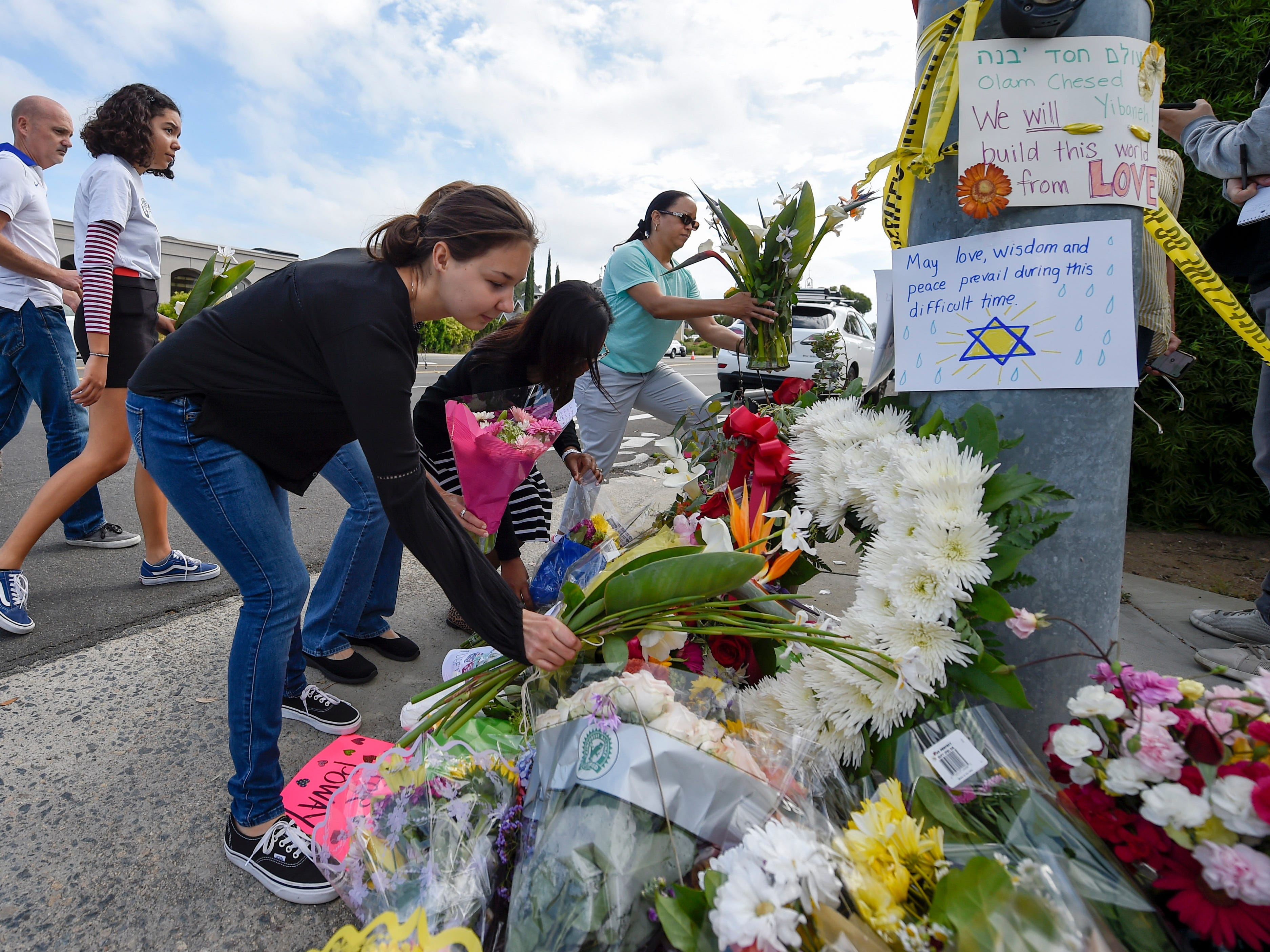 A group of Poway residents bring flowers and cards to a memorial outside of the Chabad of Poway synagogue, Sunday, April 28, 2019, in Poway, Calif. A man opened fire Saturday inside the synagogue near San Diego as worshippers celebrated the last day of a major Jewish holiday. (AP Photo/Denis Poroy) (AP Photo/Denis Poroy) ORG XMIT: CADP113
