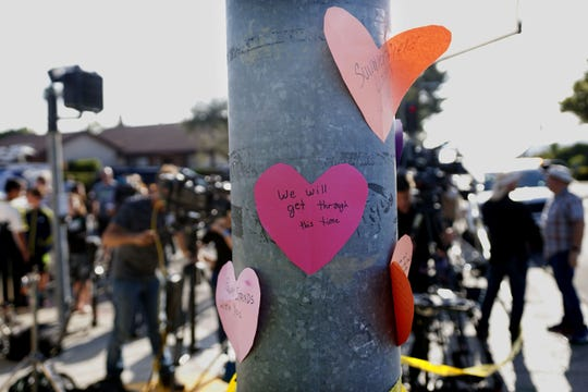 Hand-written notes are displayed on a light post across the street from the Chabad of Poway Synagogue after a shooting on April 27, 2019,