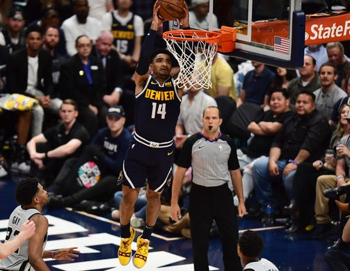 April 27: Nuggets guard Gary Harris rises up for the two-handed slam during Game 7 against the Spurs in Denver.