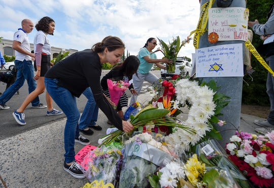A group of Poway residents bring flowers and cards to a memorial outside the Chabad of Poway synagogue on April 28, 2019.