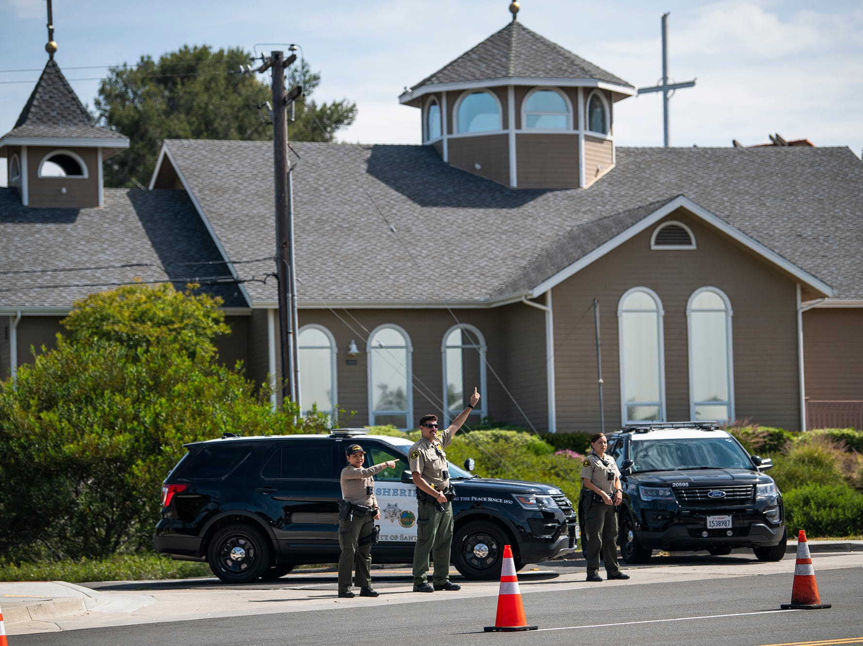 4/28/19 10:20:29 -- Poway, CA, U.S.A  -- Poway Police officers direct traffic in front of Chabad of Poway synagogue.One woman was killed and three others were wounded when a man entered a synagogue during Passover services Saturday at the Chabad of Poway temple and opened fire with an AR-style assault weapon shortly before 11:30 a.m. The suspect, 19-year-old John Earnest, was arrested and is being questioned by authorities.  --    Photo by Harrison Hill, USA TODAY Staff ORG XMIT:  HH 137983 Chabad follow 4/28/2019 (Via OlyDrop)