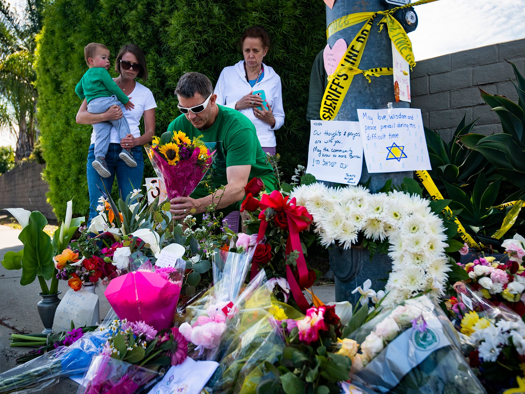 San Diego resident James Carmey places flowers at the memorial across the street from Chabad of Poway synagogue in Poway, Calif. on April 28, 2019.