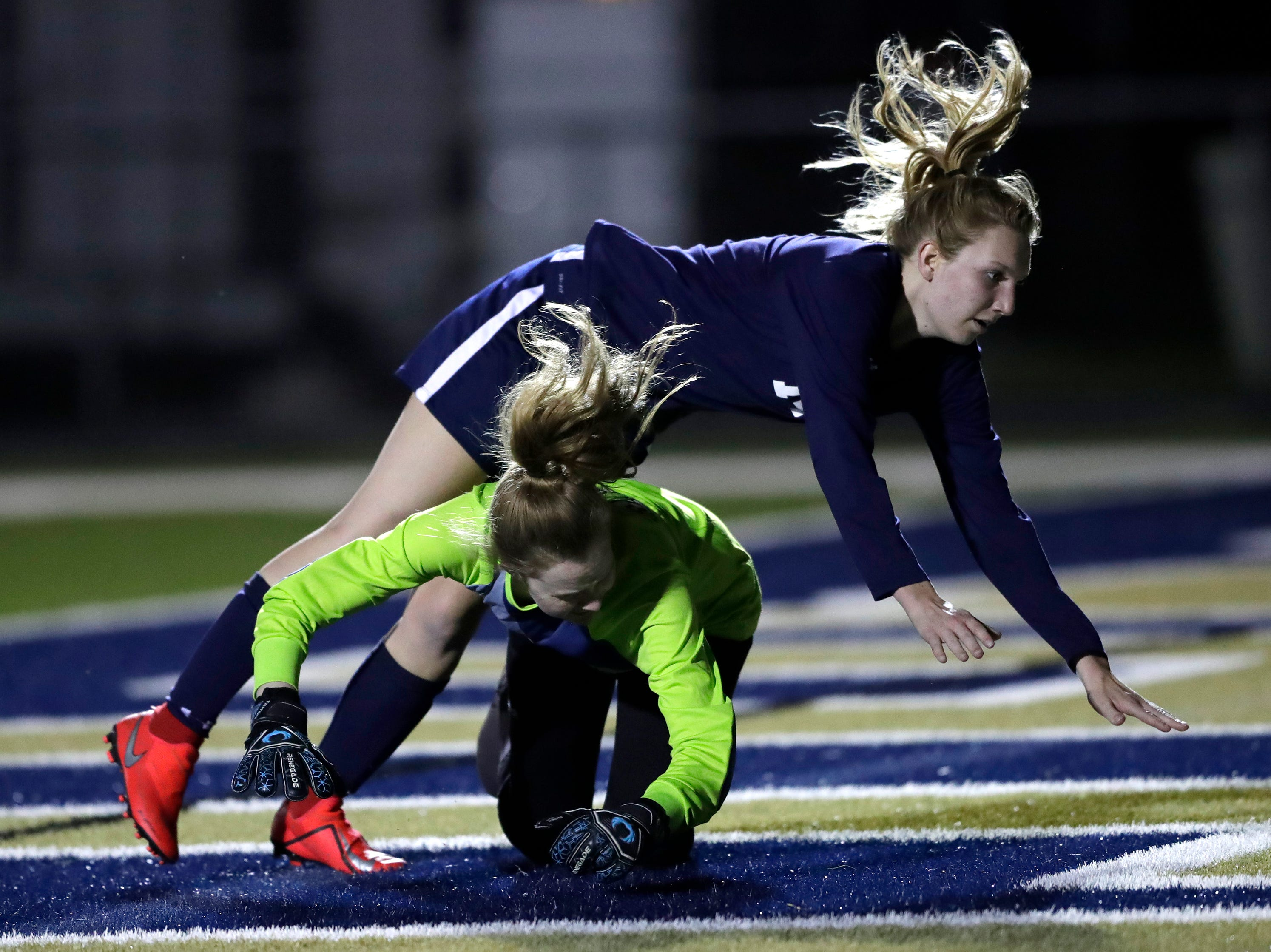 Appleton North High School's Emma Christensen (14) scores a goal as she collides with Kaukauna High School's keeper Autumn Steffens (25) during their girls soccer game Tuesday, April 23, 2019, in Appleton, Wis. 