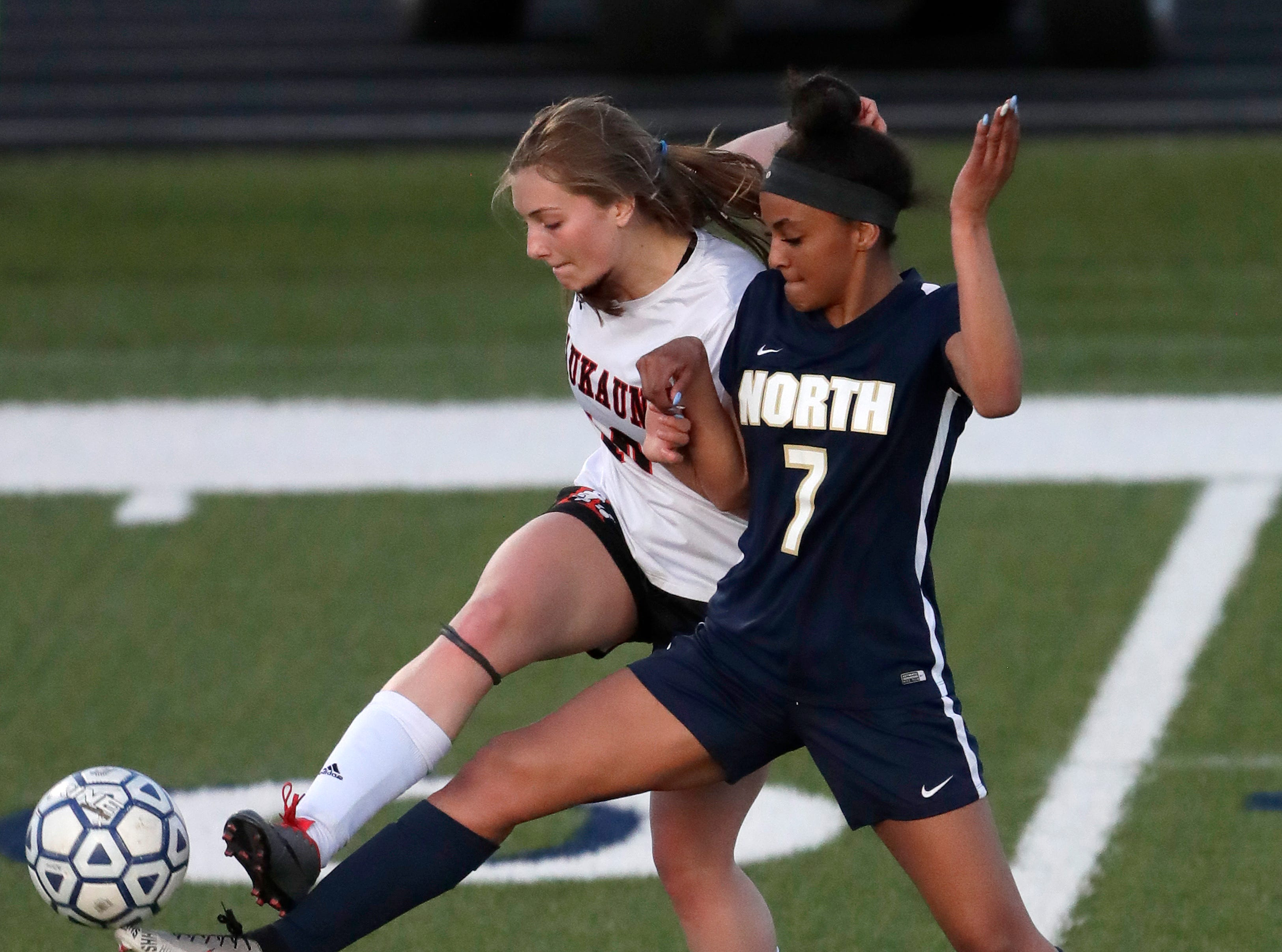 Appleton North High School's Izzie Ruzzicone (7) battles for possession of the ball against Kaukauna High School's Reece Gellerman (10) during their girls soccer game Tuesday, April 23, 2019, in Appleton, Wis. 