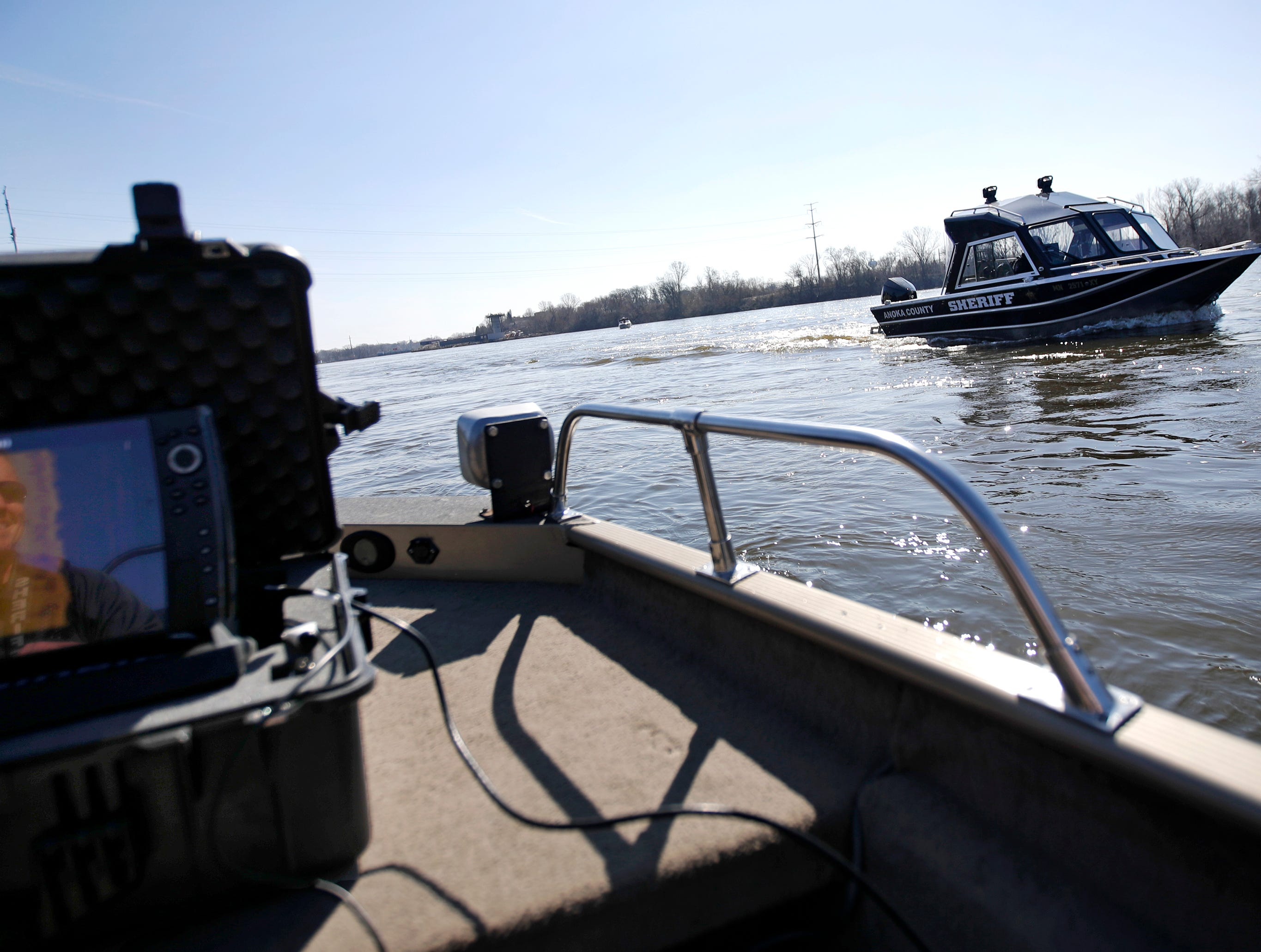 Outagamie County Sheriff's Deputy Mike Duven is reflected in a Helix 12 sonar screen after giving a thumbs up to members of the Anoka County Sheriff's Department as they pass by during training for boat sonar operations, search patterns and techniques Wednesday, April 24, 2019, on the Fox River in Kimberly, Wis. Sonar can be used in search and rescue operations as well as evidence recovery. The training involved agencies from Beaver Dam, Portage County, the Wisconsin DNR, Winnebago County, Wautoma, La Crosse and Anoka County, Minn.