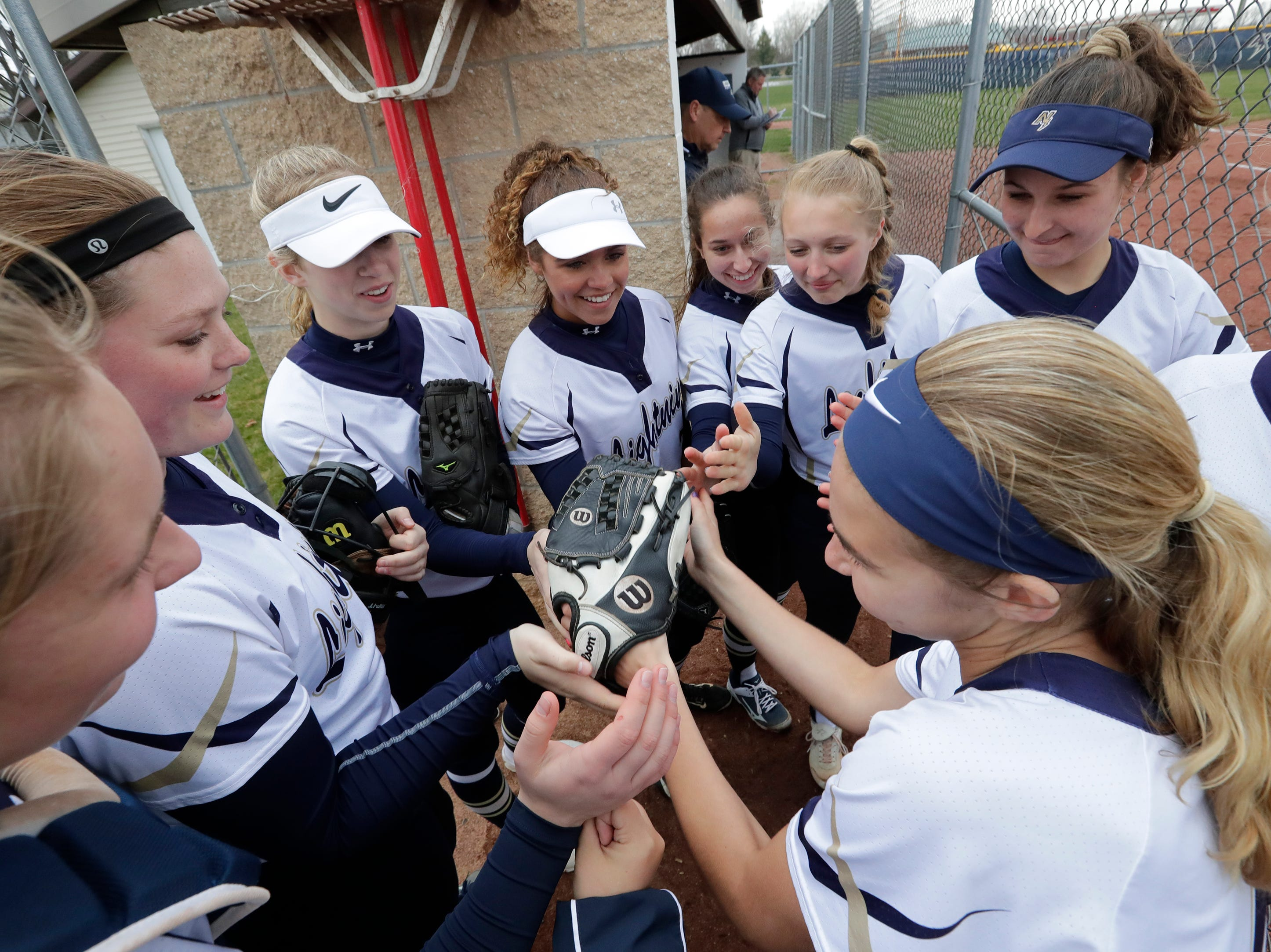 Appleton North High School's support each other as they are each announced against Hortonville High School at the start of their girls softball game Monday, April 22, 2019, in Appleton, Wis. 
