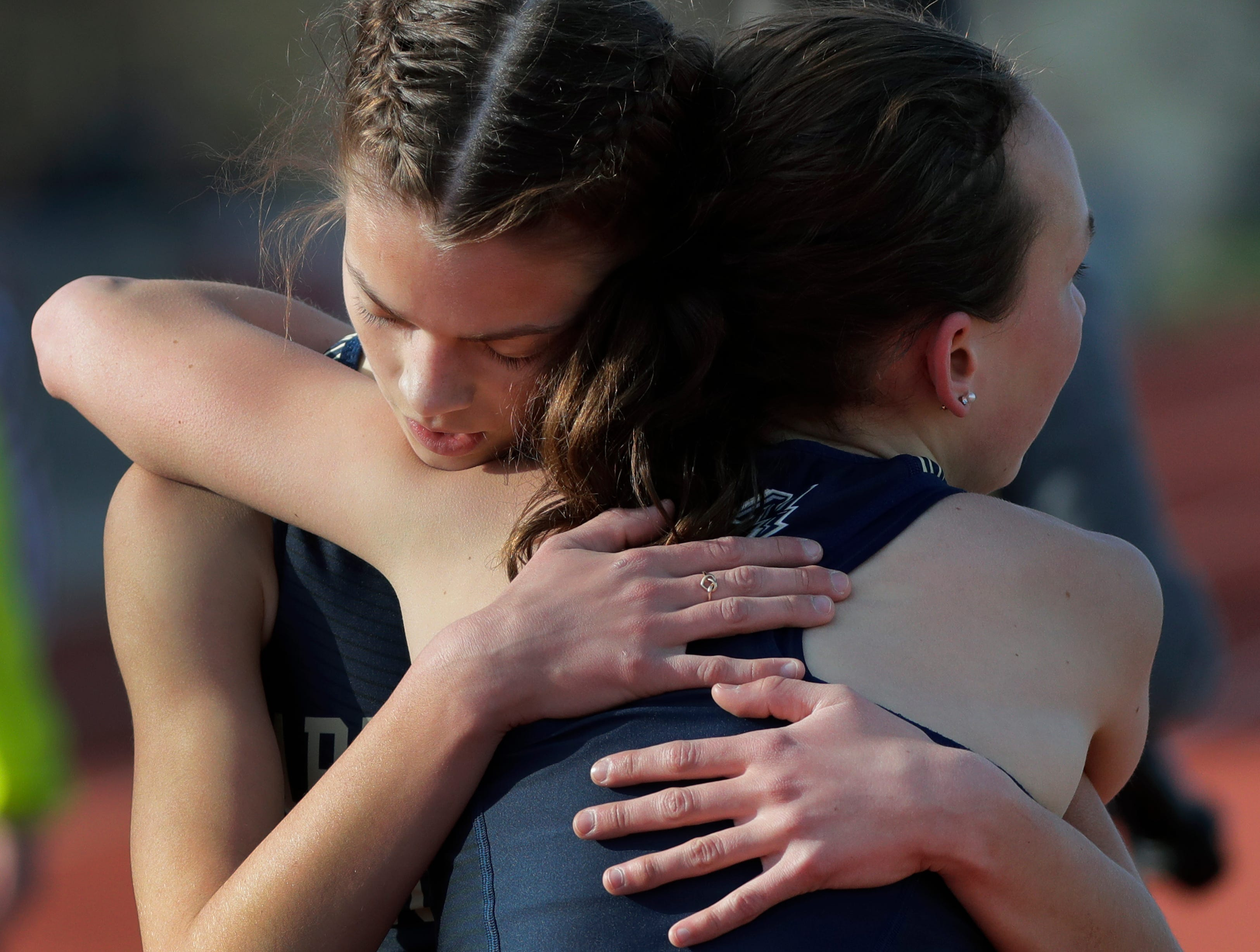 Appleton North High School's Annessa Ihde, left, gets a hug from teammate Anika Nettekoven after taking first place in the 1600-meter run during the Neenah co-ed invitational track and field meet Friday, April 26, 2019, at Neenah High School in Neenah, Wis. 