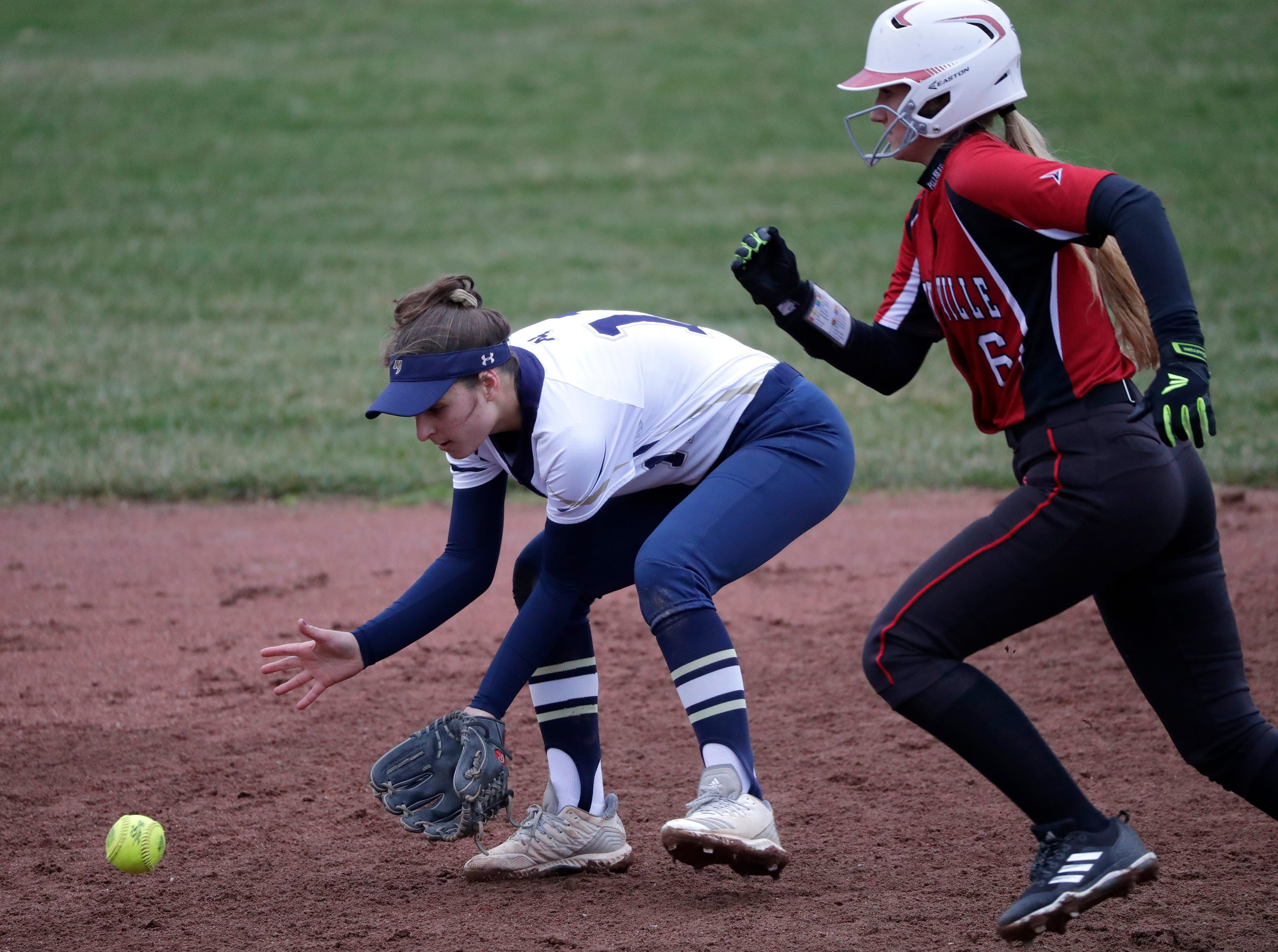 Appleton North High School's Lydia Krueger (11) fields a hit as Hortonville High School's Morgan Graybill (6) heads to third base during their girls softball game Monday, April 22, 2019, in Appleton, Wis. 