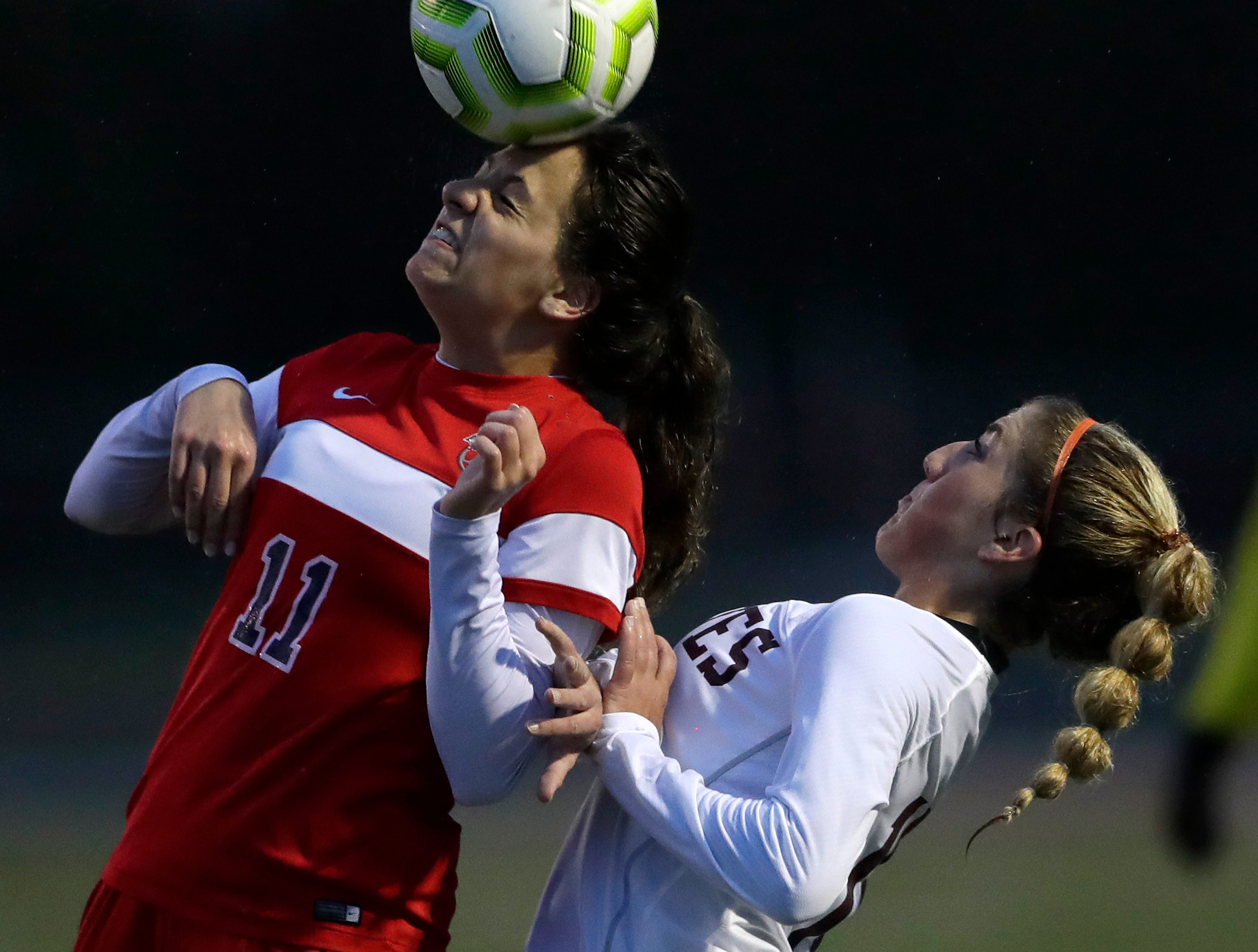 Appleton East High School's Marisa Triggiano (11) heads the ball against Winneconne High School's Alexandra Pascarella (16) during their girls soccer game Thursday, April 25, 2019, in Appleton, Wis. 