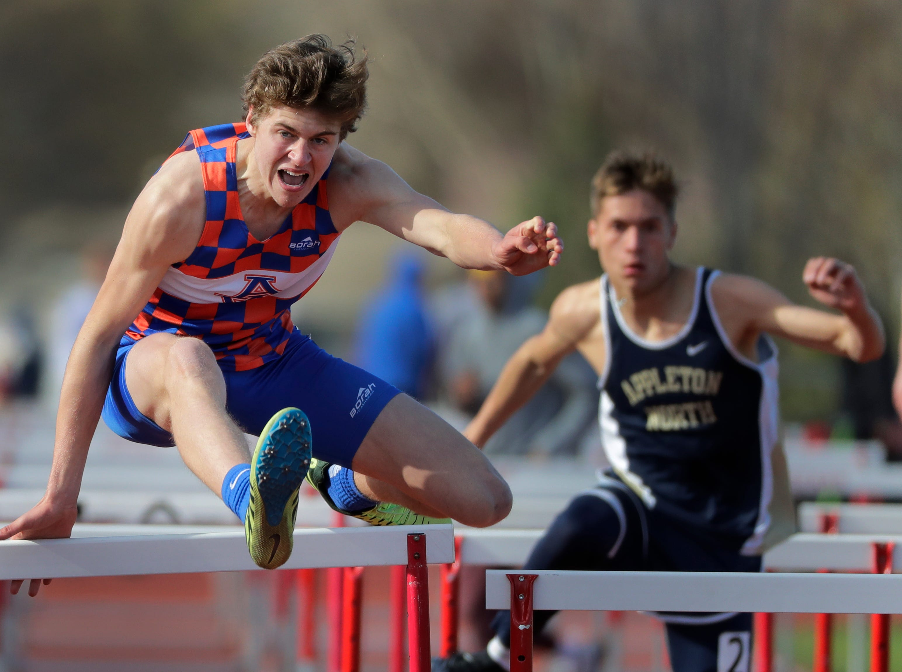 Appleton West High School's Spencer Steffen, left, competes in the 110-meter high hurdles against Appleton North High School's David Neitzke-Pizarro during the Neenah co-ed invitational track and field meet Friday, April 26, 2019, at Neenah High School in Neenah, Wis. 