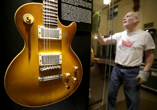 "Volunteer Dick Rank cleans a display during installation of ""Guitar: The Instrument That Rocked the World"" at the History Museum at the Castle. The exhibition will be on display at the Appleton museum through Jan. 5."