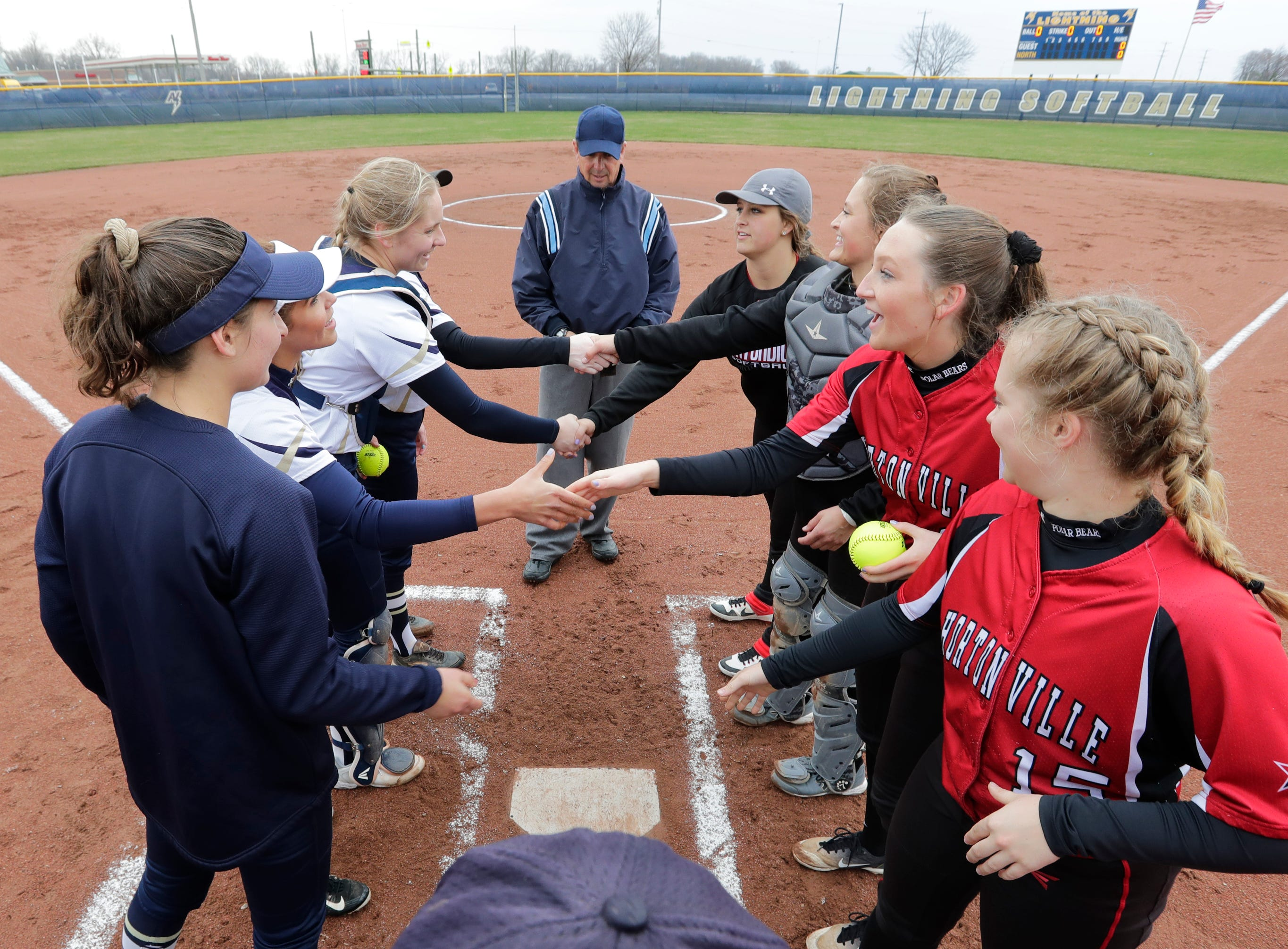 Appleton North High School's players shake hands with Hortonville High School's players at the start of their girls softball game Monday, April 22, 2019, in Appleton, Wis. 
