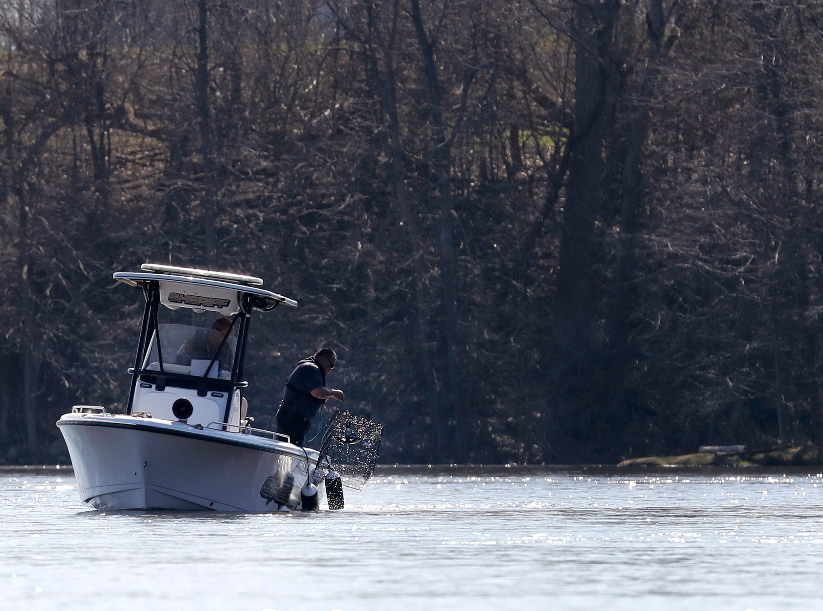 Sgt. Ker Yang, with the Outagamie County Sherif's Department, lifts a cage out of the water that was being used as a piece of training for boat sonar operations, search patterns and techniques Wednesday, April 24, 2019, on the Fox River in Kimberly, Wis. Sonar can be used in search and rescue operations as well as evidence recovery. The training involved agencies from Beaver Dam, Portage County, the Wisconsin DNR, Winnebago County, Wautoma, La Crosse and Anoka County, Minn.