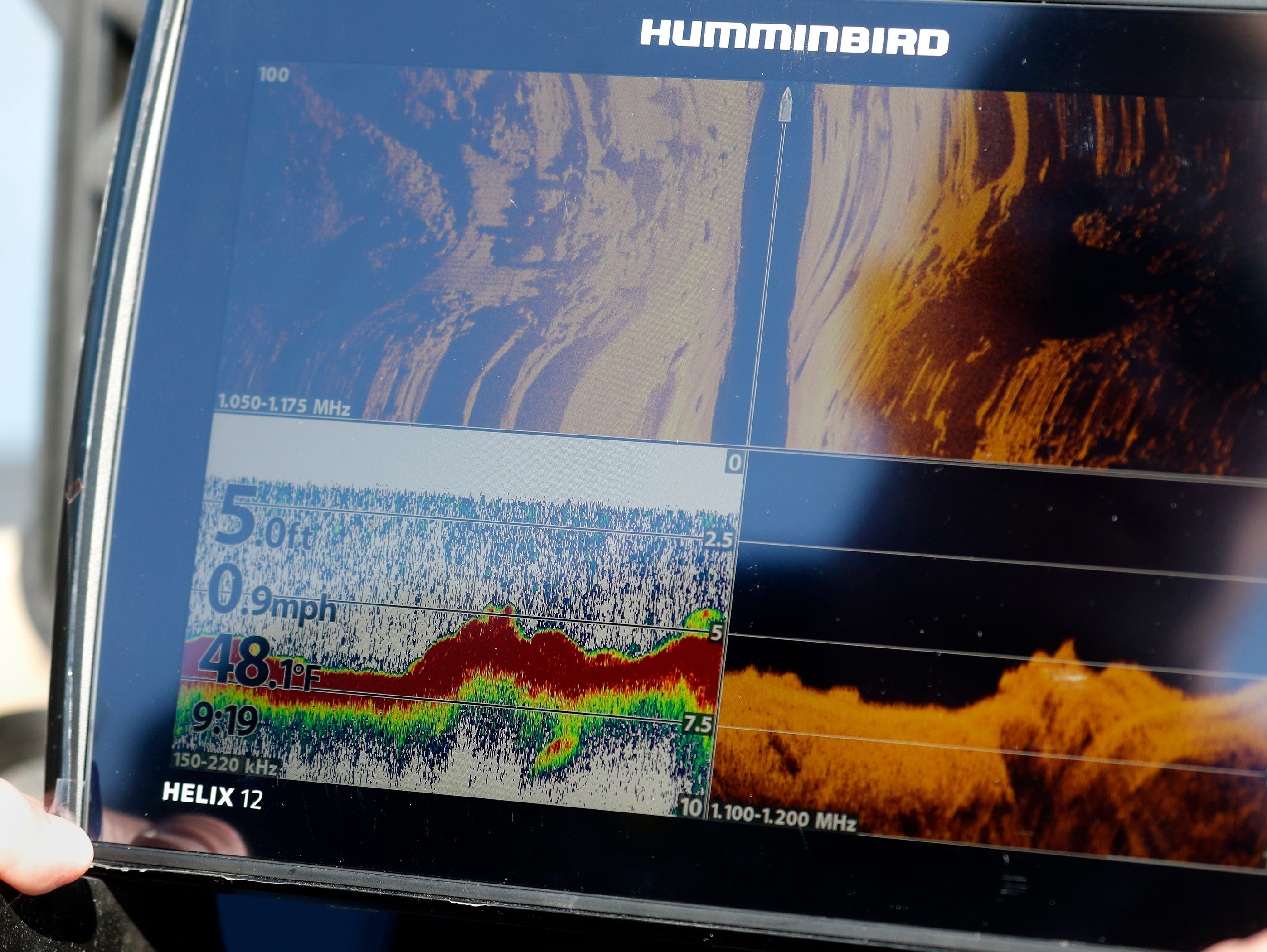 Outagamie County Sheriff's Deputy Mike Duven is reflected in a Helix 12 sonar screen as he prepares it for training on the Fox River after leaving Sunset Park Wednesday, April 24, 2019, in Kimberly, Wis. The training involved agencies from Beaver Dam, Portage County, the Wisconsin DNR, Winnebago County, Wautoma, La Crosse and Anoka County, Minn.