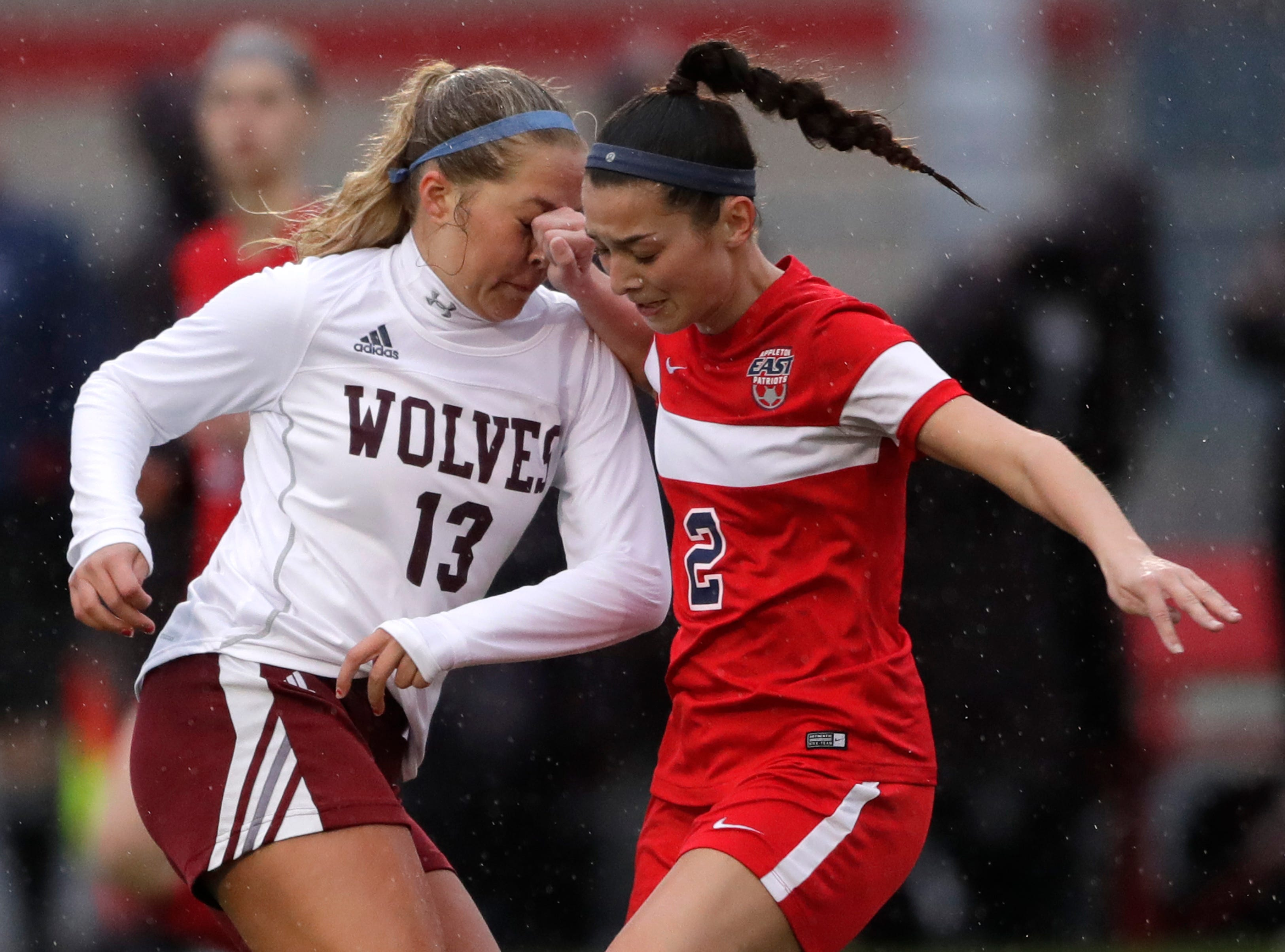 Winneconne High School's Senya Josephson (13) takes a fist to the nose as she tries to cut back against Appleton East High School's Ellie Behnke (2) during their girls soccer game Thursday, April 25, 2019, in Appleton, Wis. 