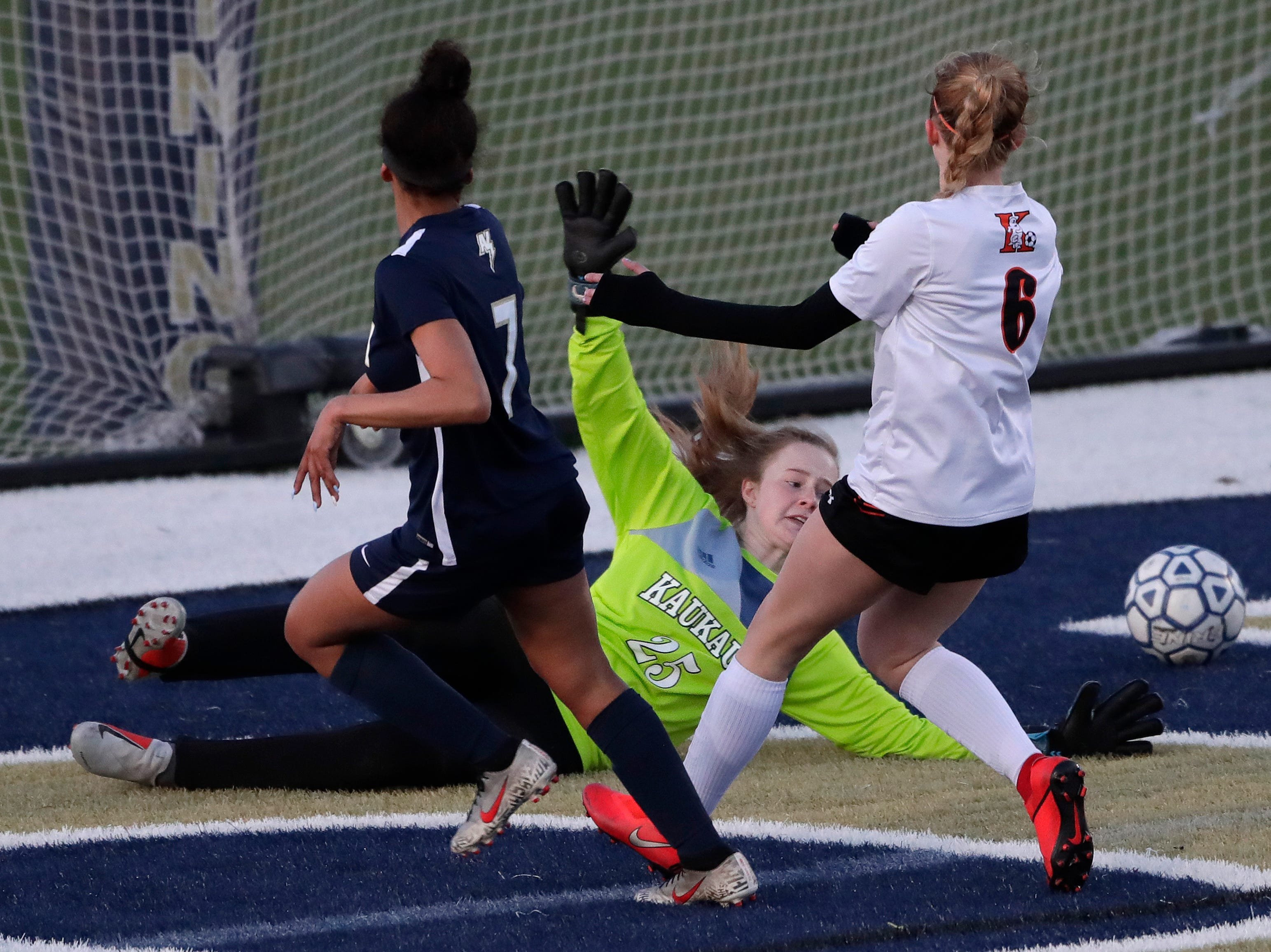 Appleton North High School's Izzie Ruzzicone (7) scores a goal against Kaukauna High School's keeper Autumn Steffens (25) and Meradith Schaller (6) during their girls soccer game Tuesday, April 23, 2019, in Appleton, Wis. 