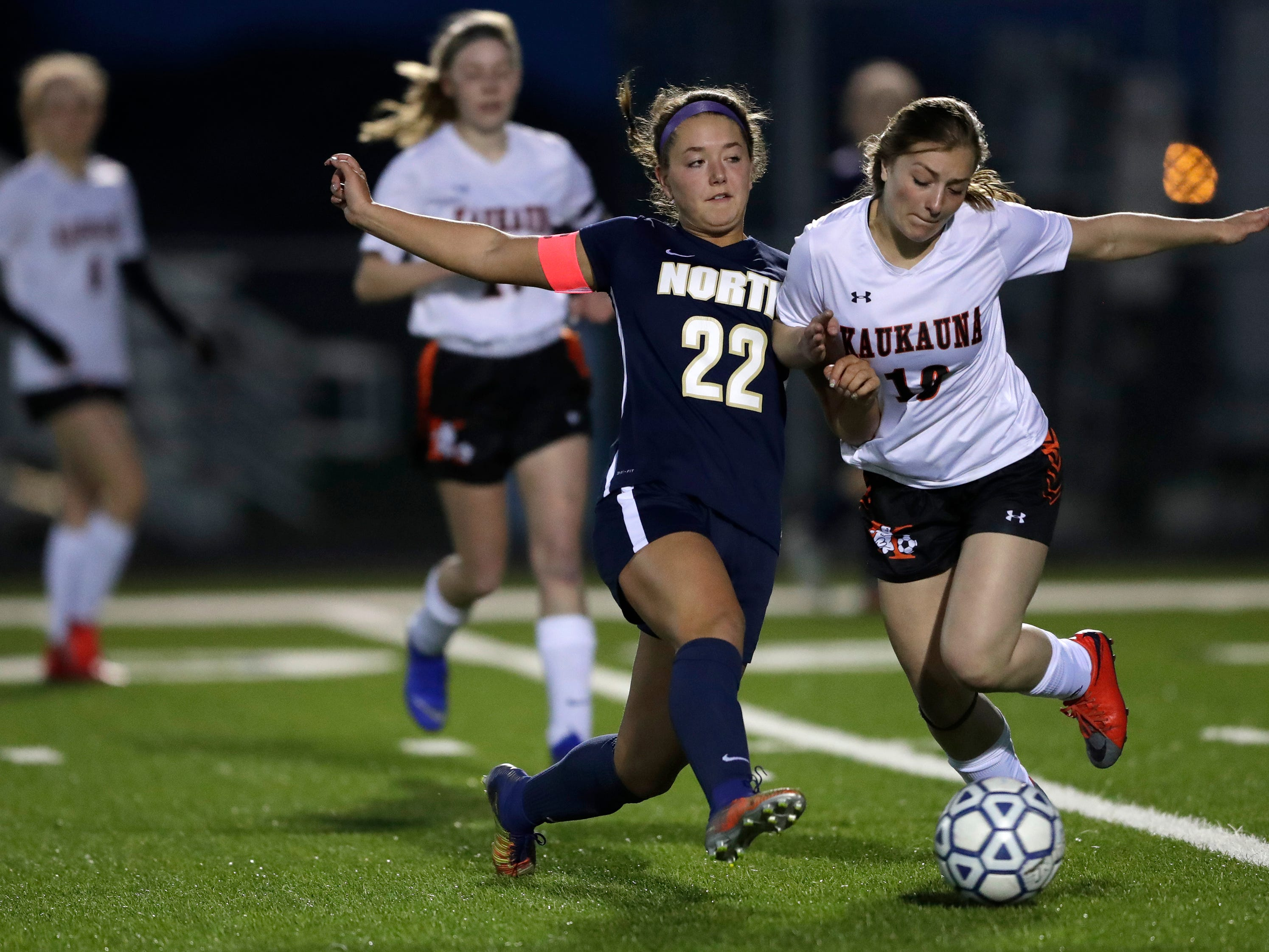 Appleton North High School's Taylor Tomoda (22) passes the ball against Kaukauna High School's Reece Gellerman (10) during their girls soccer game Tuesday, April 23, 2019, in Appleton, Wis. 