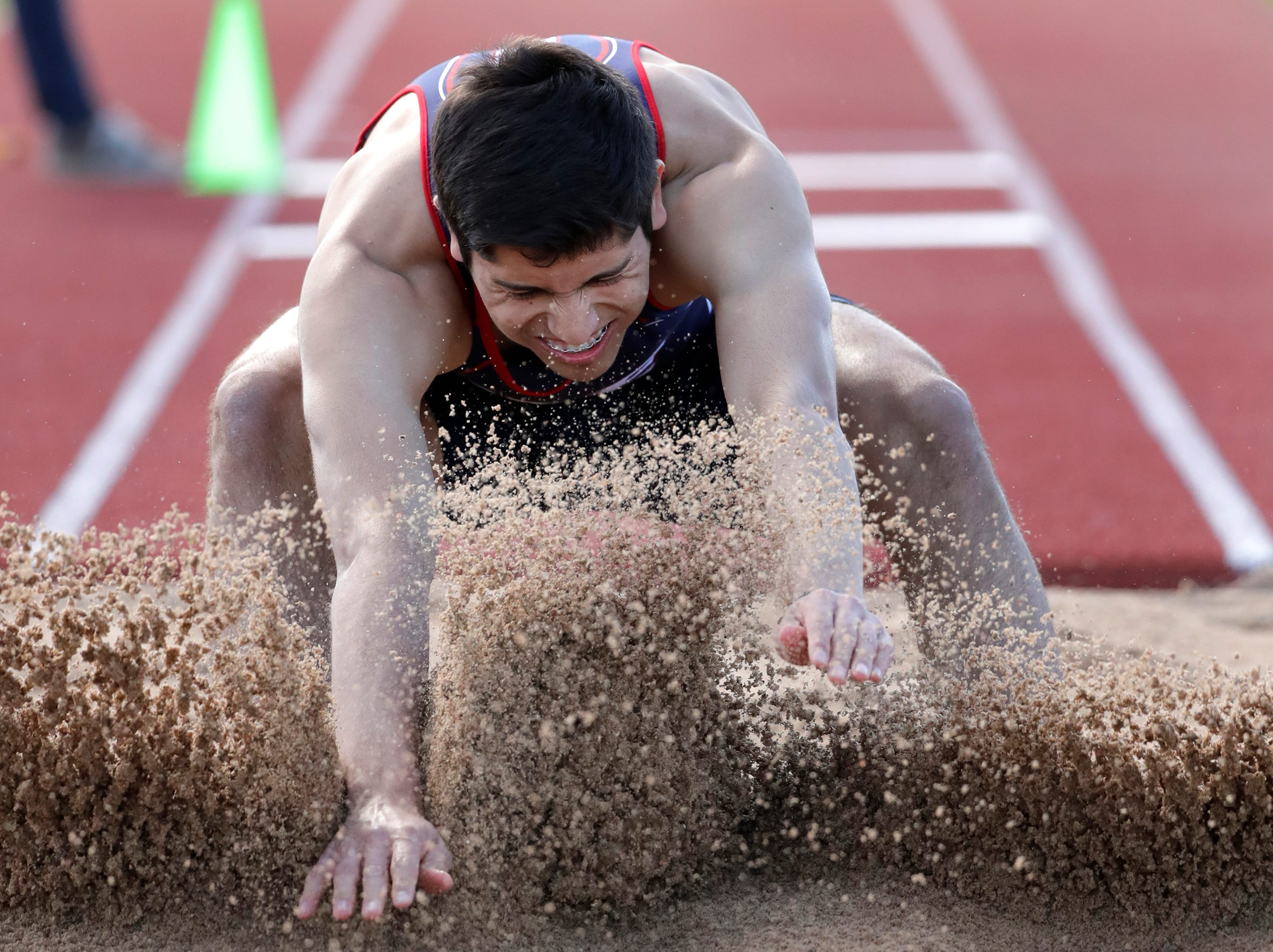 Appleton East HIgh School's Mario Mendoza competes in the triple jump during the Neenah co-ed invitational track and field meet Friday, April 26, 2019, at Neenah High School in Neenah, Wis. 