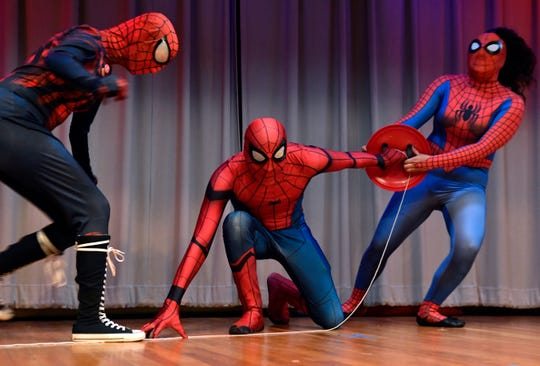 Cassey Davis (left), Mark Ramirez, and Alexa Mendoza duel over Captain America's shield in a Spider-Man Spiderverse cosplay skit onstage at the Abilene Public Library's main branch on Saturday. The trio performed for the audience as judges were tallying their votes for the Libcon cosplay costume contest.