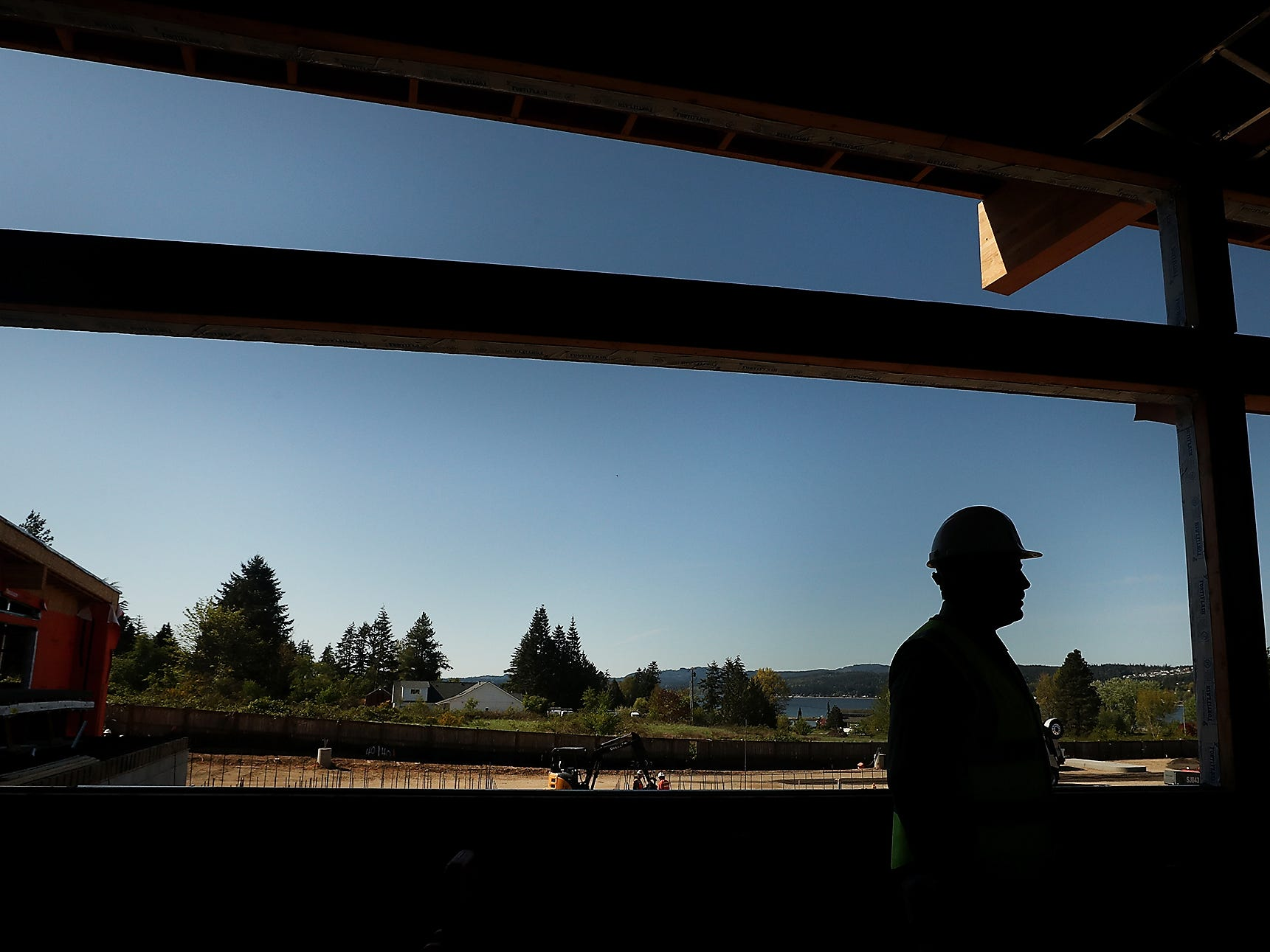 """Maynard's owner and executive chef JJ Meland is silhouetted against one of the large windows as he gives a tour of the building under construction on Bucklin Hill in Silverdale on Monday, April 29, 2019. Dubbed """"Kitsap's Culinary Destination"""" the enterprise will be a restaurant, market and distillery."""