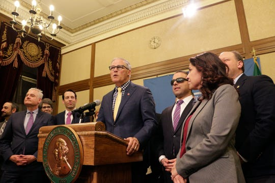 Gov. Jay Inslee, surrounded by Democratic lawmakers from the Senate and House, talks to the media following the Washington Legislature adjourning its 105-day legislative session early Monday in Olympia. Lawmakers passed a new, two-year budget before adjourning for the year.