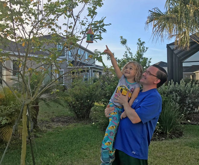 Isabella points to the bird house that she had just hung from the limb of a tree in our backyard.