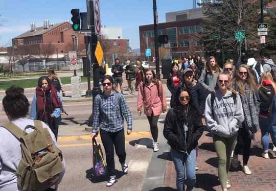 Students from University of Vermont cross Main Street at University Heights on Monday, April 29, 2019.