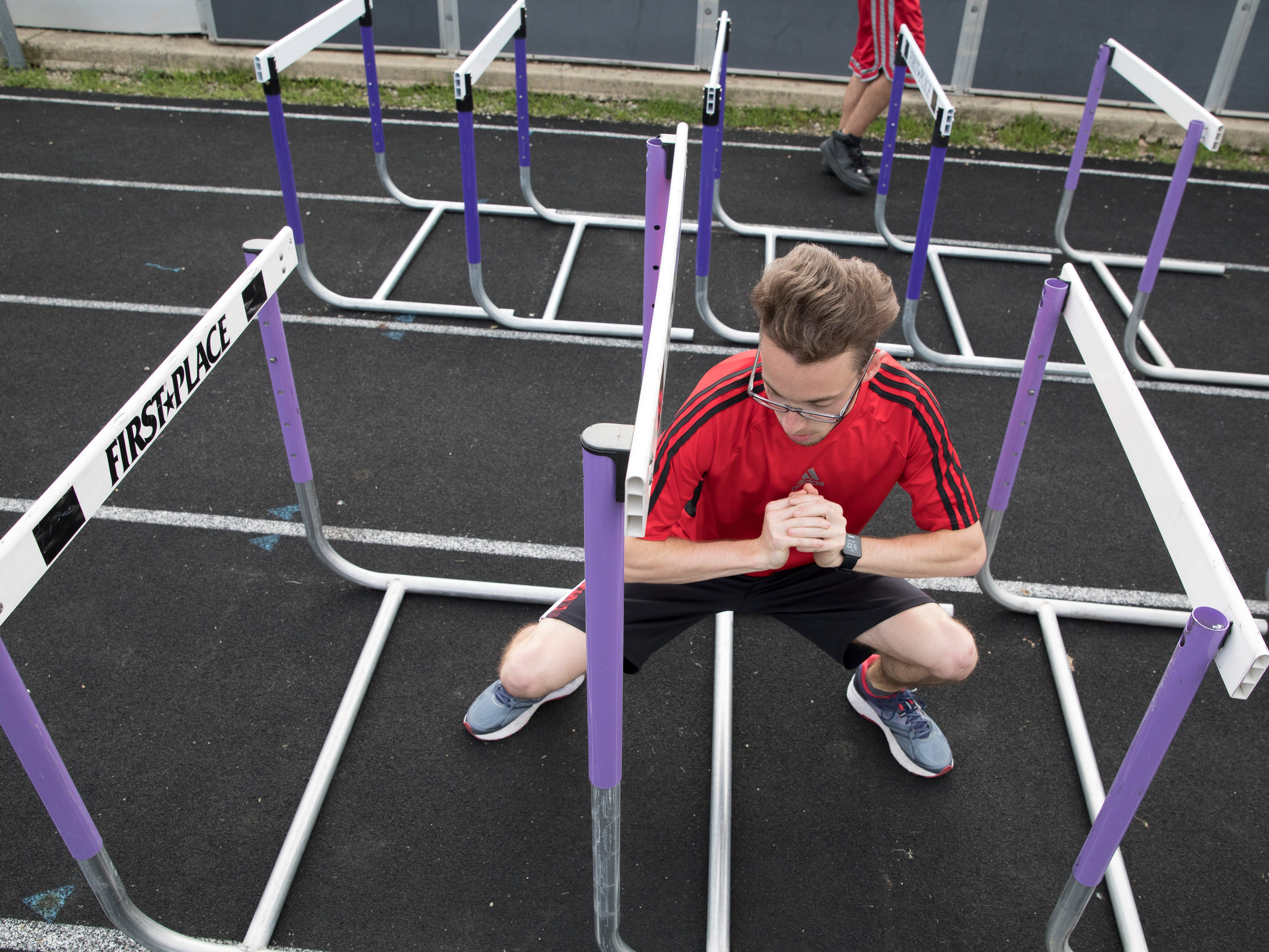 With the aid of hurdles, Eric Hacker does stretching exercises to improve his mobility and performance during practice at Unioto High School.