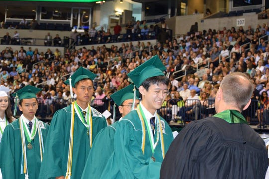 Alvin Zhang, Mason High School's 2016 valedictorian, accepts his diploma during that year's graduating ceremonies.