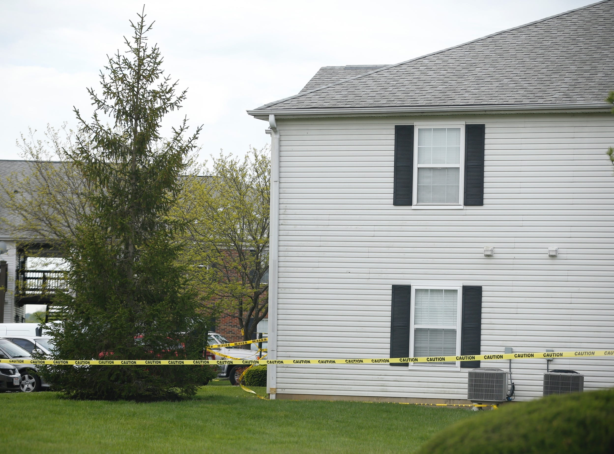 Police tape surrounds a West Chester Township apartment where 4 people were found dead Sunday night