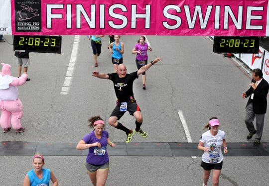 Rob McCormack of Nebraska clicks his heels as he finishes the half-marathon in the 16th annual Cincinnati Flying Pig Marathon on May 4, 2014. There were nearly 20,000 runners competing in the half-marathon, marathon and relay races.