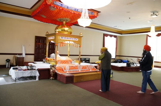 Gurmeil Singh, left, and Jasminder Singh, pray at the Guru Nanak Society of Greater Cincinnati West Chester Monday, April 29, 2019. Jasminder Singh said one of the people found dead Sunday night was Hakikat Singh Panag, whom he  knew for 11 years. Police have not confirmed Panag's name. Four people were found dead at Lakefront at West Chester apartment complex, according to police.