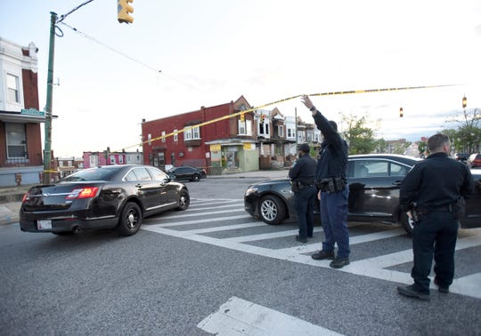 Police work near the scene where authorities say several people were shot, at least one fatally, Sunday, April 28, 2019, in Baltimore.