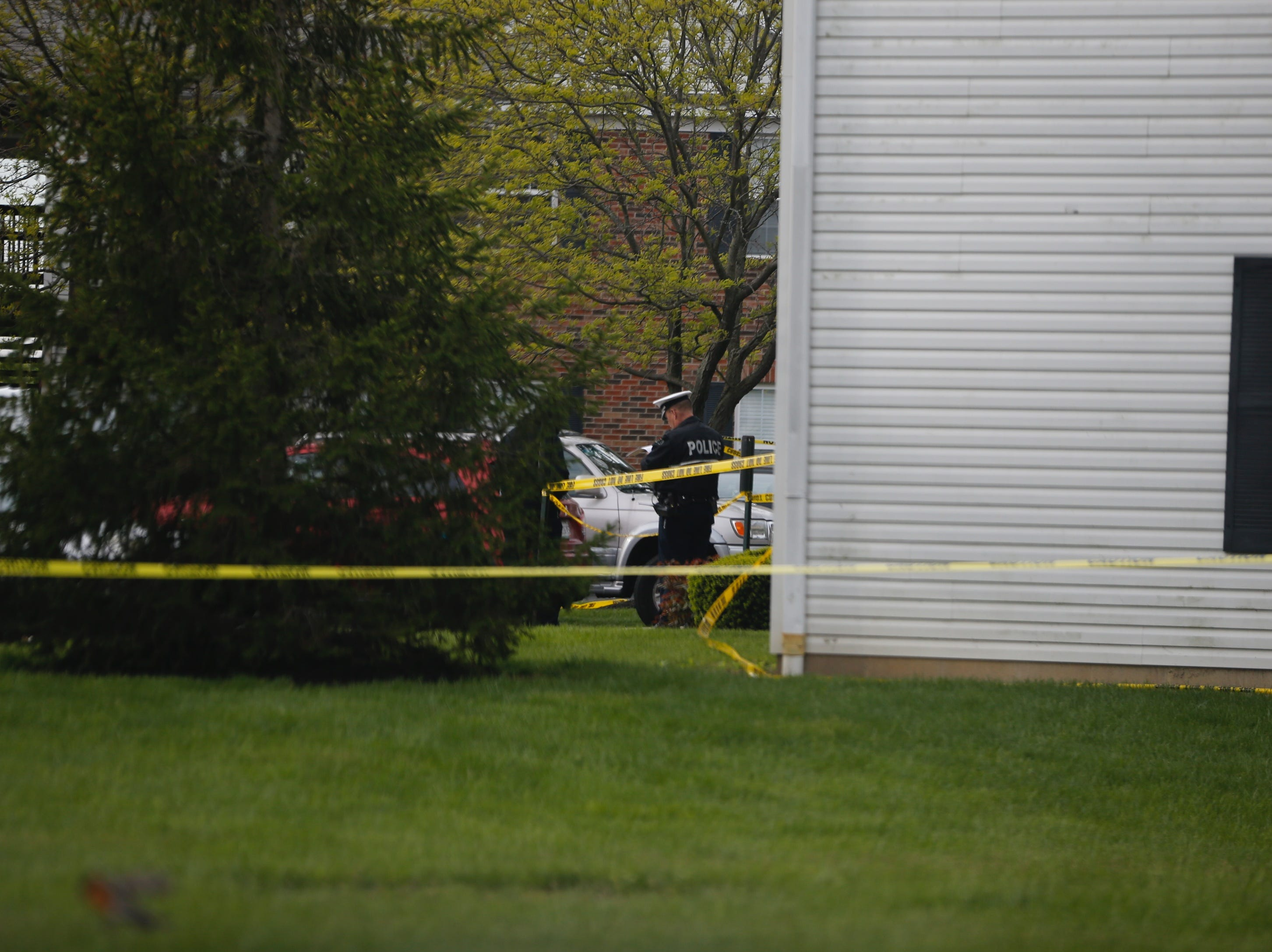 A police officer is seen Monday morning near an apartment where 4 people were found dead Sunday night.