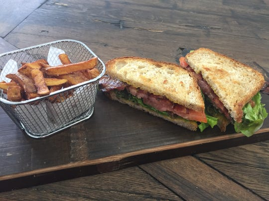 A BLT with preserved egg and house-made bacon at Rinds, Wines, & Swines, along with fries cooked in lard