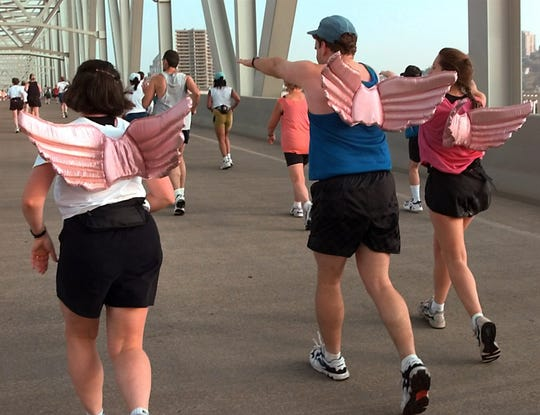 With their pig wings on, three runners fly across the Taylor-Southgate Bridge as the Flying Pig Marathon continued after the 5-mile mark Sunday. From left, Lindsay Campbell, of Kirkland, Washington, Jim Kohl, center, and Tracey Miller, of Columbus, Ohio.