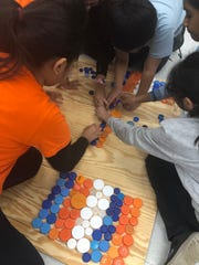 In celebration of Earth Day, the SmartTech classes at Thomas Edison EnergySmart Charter School created a TEECS logo sign made out of recycled bottle caps. Each class had a part in sorting caps by color and glueing them onto the boards. On Tuesday, April 23, the school hung them on the fence of the soccer field.