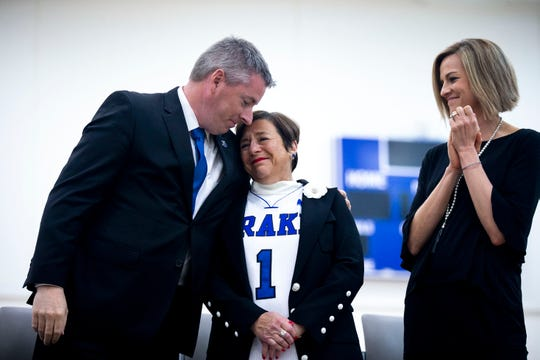 Brian Hardin, Drake University director of athletics, embraces Suzie Glazer-Burt, philanthropist and longtime supporter of Drake, as Drake Women's Basketball Coach Jennie Baranczyk looks on, during a ceremony to announce Glazer-Burt's donation of $5 million to the women's basketball program on Monday, April 29, 2019, on the Drake campus in Des Moines.
