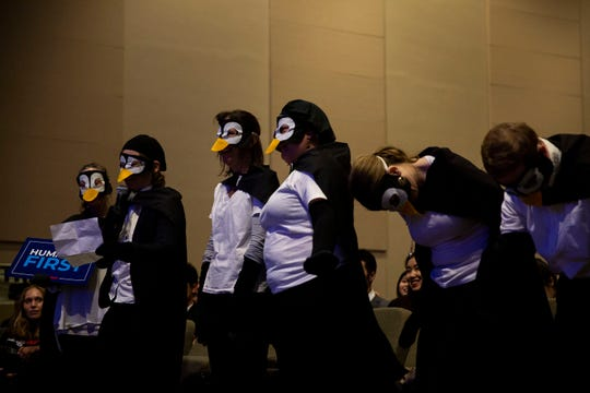 A group of Iowans dressed as penguins asks Andrew Yang, entrepreneur and 2020 caucus candidate, about climate change during a town hall on Sunday, April 28, 2019, at Franklin Junior High School in Des Moines.