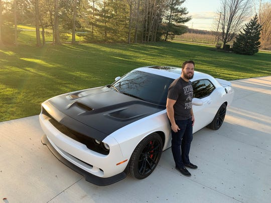 Val Saph can be seen in front of his home in Armada next to his beloved Challenger Hellcat on April 23. The financial analyst working for Fiat Chrysler drives the muscle car in The Challenger Hellcat flushes the stress away every day, says the competitor.