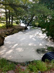 PFAS foam pools from a stormwater outfall near the former Wurtsmith Air Force base in Oscoda, entering northern Van Etten Lake, in this September 2018 photo.