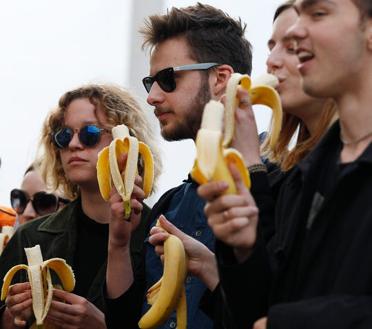 People with bananas demonstrate with others outside Warsaw's National Museum.