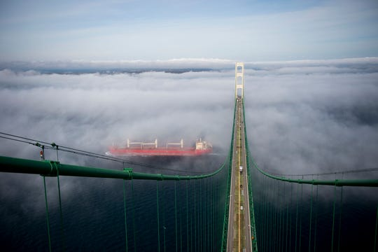 Scenic, Straits Of Mackinac, Mackinac Bridge, shot from the South Tower, looking at the North Tower in the directon of St. Ignace with heavy fog washing over the bridge deck, Salt Water Freighter going under the bridge.