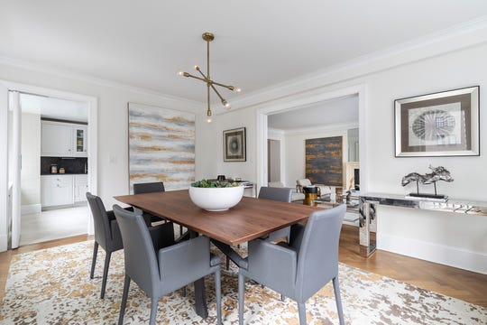 Gray chairs paired with a blend of gray and gold accents in an area rug and artwork add interest in this dining area.
