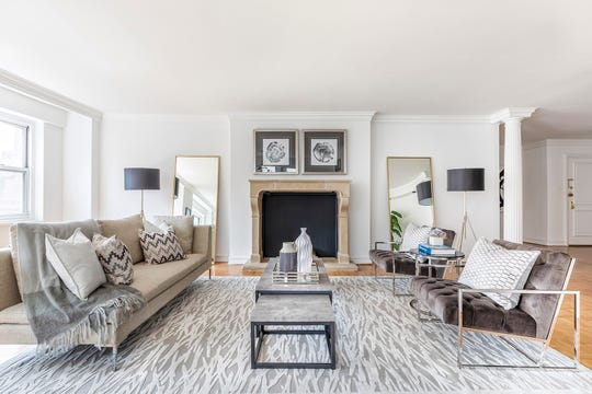 Various shades of gray in an area rug, chairs and tables blend to create a soothing living room space.